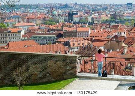 young woman looking on the old town of Prague from the observation deck
