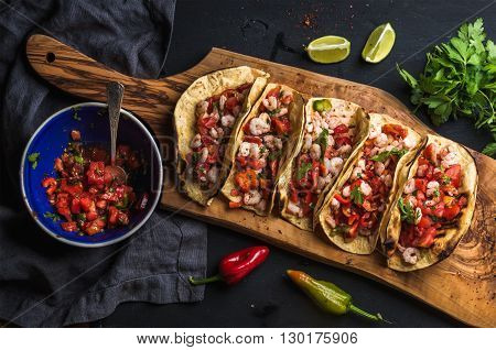Shrimp tacos with homemade salsa, limes and parsley on wooden board over dark background. Top view. Mexican cuisine