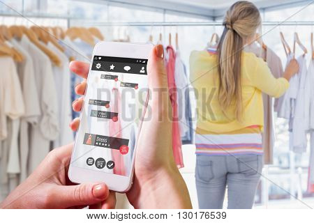 Hand holding smartphone against bored man while his girlfriend is shopping