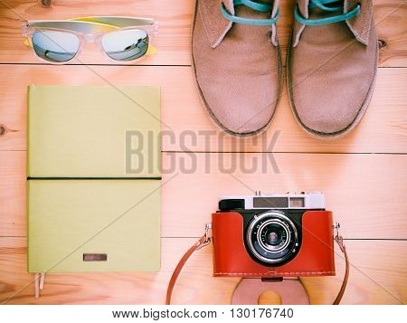Set of travel and resort stuff. Old 35 mm camera, note book, sunglasses and desert boots on wooden table. Top view, flat lay