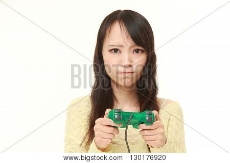 portrait of young Japanese woman losing playing video game on white background