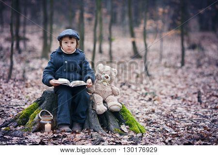 Cute Little Child, Sitting On A Tree Trunk With His Teddy Bear