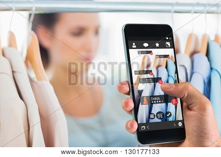 hand holding smartphone against digital image of shopping online