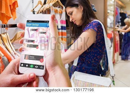 Hand holding smartphone against woman with bag looking through clothes