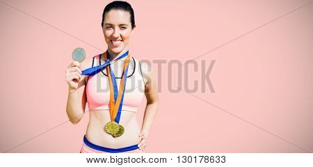 Portrait of happy sportswoman showing her medals against light pink