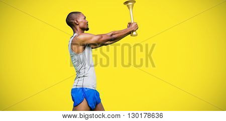Profile view of sportsman holding a cup against yellow background