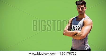 Portrait of handsome sportsman is posing with crossed arms against green background