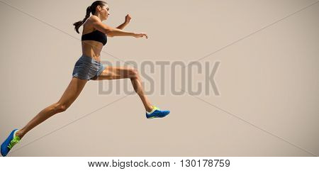 Profile view of sportswoman jumping against beige background
