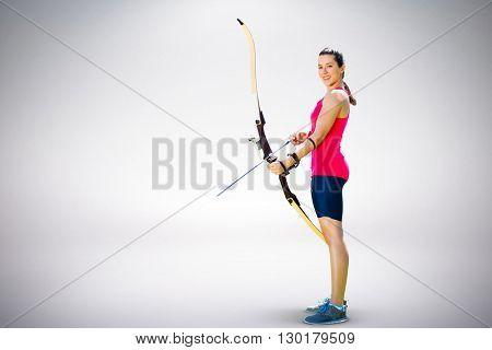 Sportswoman practicing archery against grey background