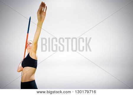Sporty woman preparing her javelin throw against grey background