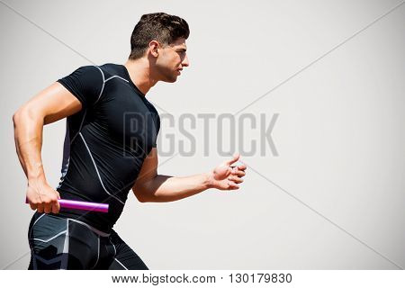 Athletic man running a relays against grey background