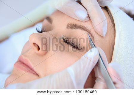 Young woman plucking eyebrows with tweezers close up.