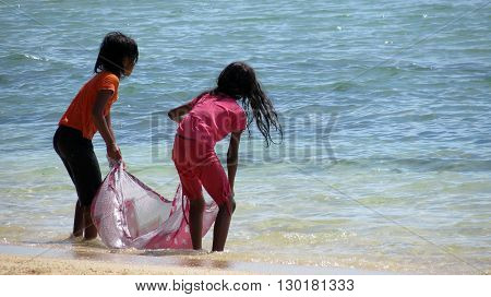 Andaman-Apr 24: Two girls playing on a beach and trying to catch sea waves, Wandoor Island, Port Blair Apr 24, 2012 in Andaman and Nicobar Islands, India, Asia.