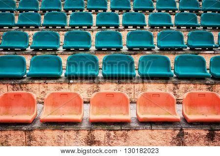 Empty old plastic seats at stadium open door sports arena.
