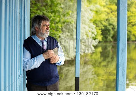 Old Man With A Book On A Porch