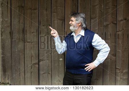 Elderly Man Standing Outside On Wooden Background