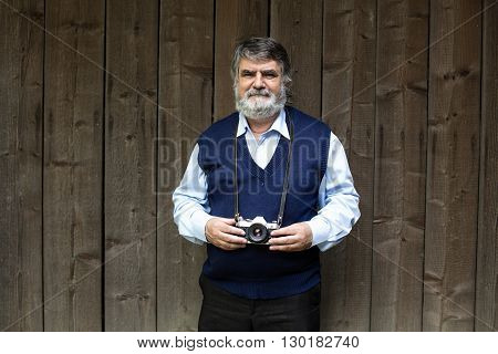 Old Photographer Standing On Wooden Background