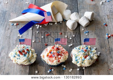 Marshmallows and cupcakes with American Flags for the 4th of July on wooden surface