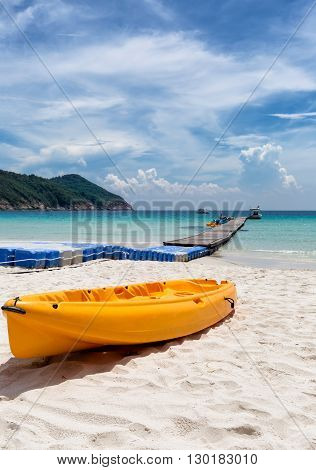 Orange canoe kayak boat lying on a tropical beach