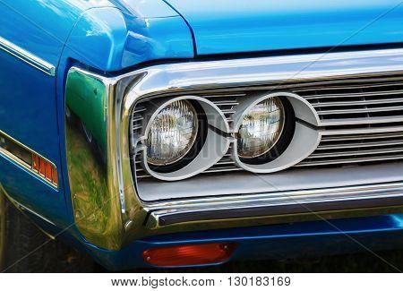 Headlights of blue retro car. Retro styled blue classic car. Selective focus.