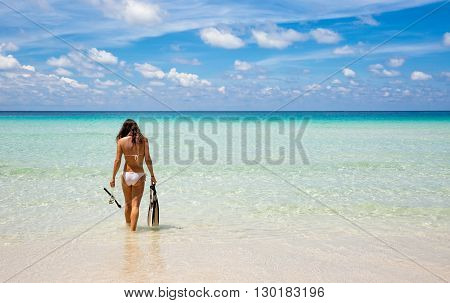 Woman goes for snorkeling into the turquoise sea of Malaysia, Island of Redang