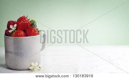 Fresh berry in old aluminum mug  on white marble table with blue background
