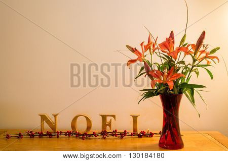 Christmas decoration of Noel with vase of iris flowers