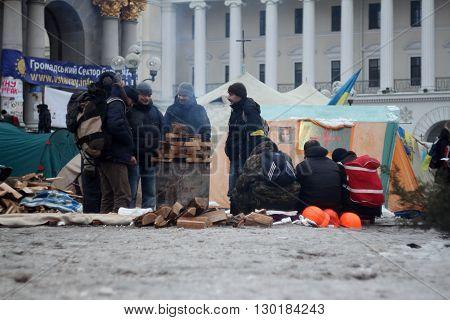 Kiev, Ukraine - December 11, 2013: Mass anti-government protests EuroMaydan in the center of Kiev (Maidan Nezalezhnosti). Protesters are heated by the fire on December 11, 2013 in Kiev, Ukraine