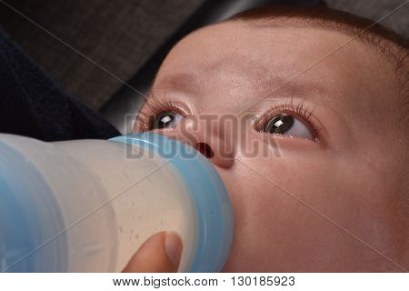 Mother feeding baby boy with a plastic baby bottle.