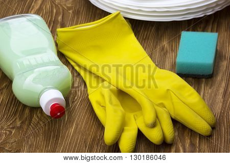 Detergent, sponge, dishes and latex gloves on wooden background