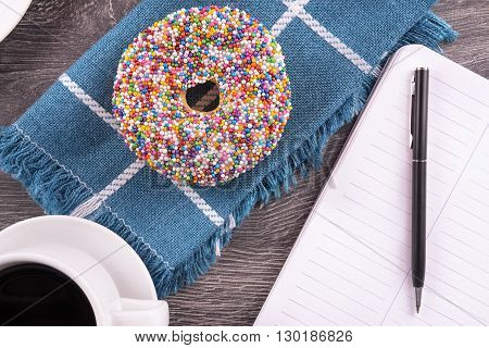 Donut and coffee cup on wooden table, top view.
