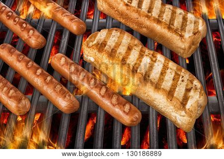 Sausages and hot dog buns over a hot barbecue grill.