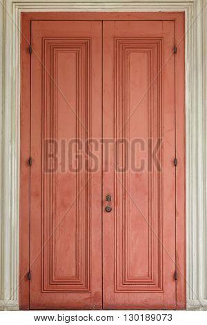 Ancient red door with white door frame.