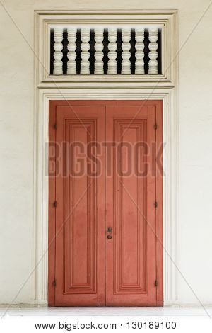 Ancient red door with white door frame and air passage.