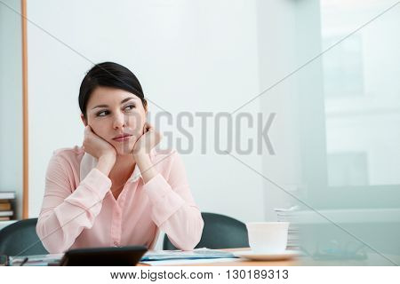 Beautiful woman dreaming at working place