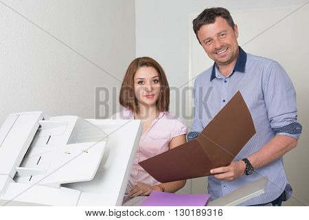 Businessman And Woman Using A Copy Machine Smiling