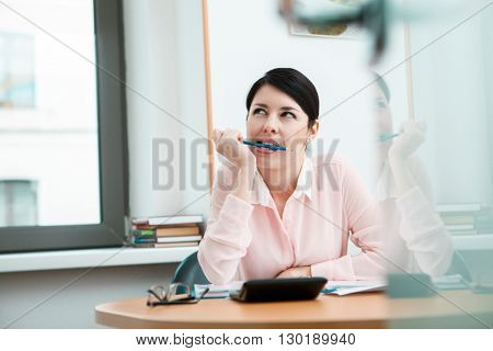 Young office worker dreaming in her workplace
