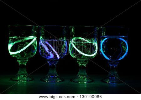 Four neon glowing party drinks illuminated in the nightclub.