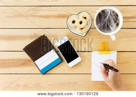 Hand Writing Down On Blank Note Paper With White Cup Of Black Coffee And Mobile Phone And Blank Card