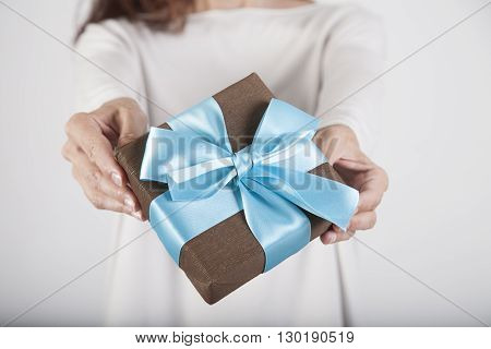 brown gift box with blue ribbon in woman blue jeans cream jersey hands over white background