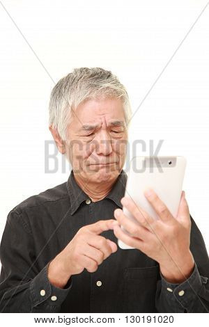 portrait of senior Japanese man using tablet computer looking confused on white background