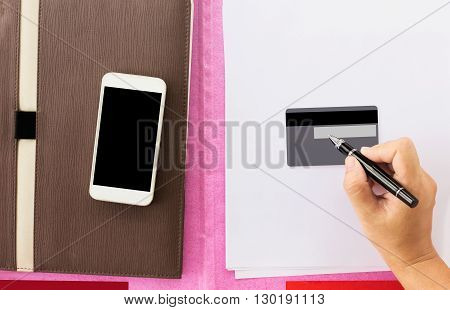Hand With Pen Sign Or Writing Down At The Back Of Blank Siganature Or Sign Area On Debit Or Credit C