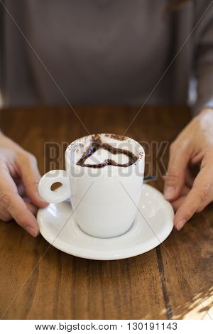 white small cup cappuccino coffee with chocolate heart in woman hands on light brown wooden table