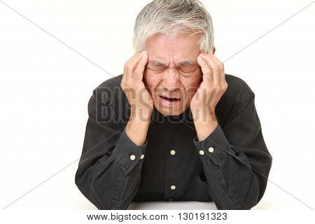 portrait of senior Japanese man suffers from headache on white background