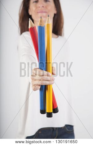 closeup of blue red and yellow primary colours big pencils in woman hand fingers isolated over white background