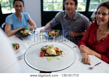 Waiter serving meal to group of friends in a restaurant