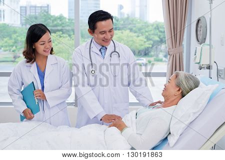 Vietnamese doctor and nurse talking to senior patient in ward