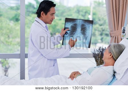 Vietnamese doctor showing x-ray to mature patient