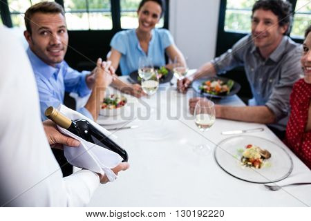 Waiter carrying a wine bottle for a group of friends sitting in a restaurant