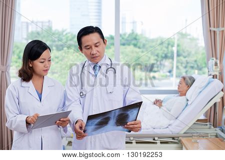 Serious Vietnamese doctor and nurse examining x-ray of aged woman